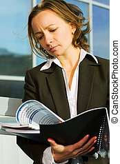 Businesswoman reading a reports - Young businesswoman...