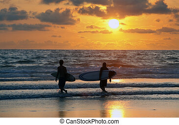 surfers at red sunset - Silhouettes of three surfers at red...