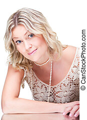 Portrait of coquettish beautiful young blonde woman wearing knitted lacy dress with pearl beads and bracelet on isolated white background