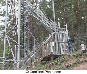 Metal observation deck in nature - People climb stairs to...