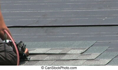 Man Roofing A Roof - A man uses a nail gun to lay shingles...
