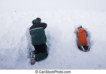 Winter play - A boy and his father digging the snow cave