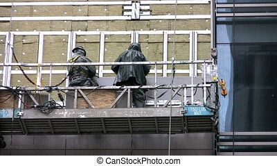 Workers On Platform - Two workers attach building siding on...
