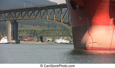 Tugboat Passes Under Bridge - A tugboat passes under a...