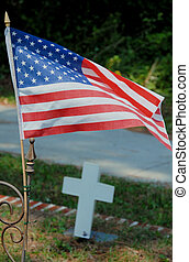 US Flag - A small United States flag over a grave with a...