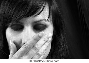Young girl covering her mouth with her hand in black and...