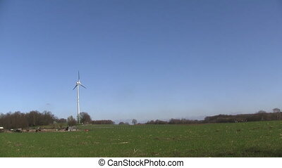 Wind turbine on a clear blue sky close to a forest
