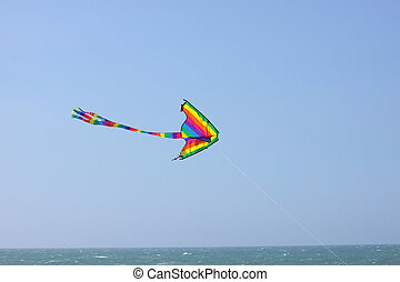 kite in a blue sky above the sea