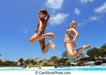 boy with mum jumping into the pool smiling - boy with mum...