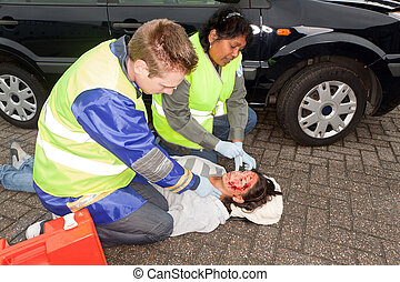 Paramedics in action - Paramedics checking a woman injured...