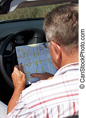 Mature man reading a map - Mature man sitting in a car...
