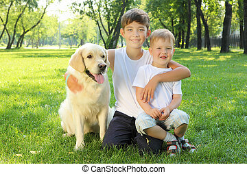 Two brothers in the park with a dog