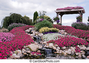 country garden with waterfall - Colorful petunias and...