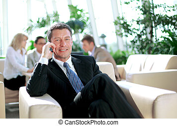 Concentrating businessman on call, coworkers talkling in...