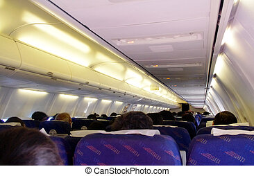 Inside plane cabin - Passengers sitting in the cabin of an...