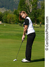Putting - Adult female golfer putting on the green