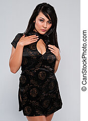 Cheongsam - Pretty young multiracial woman in a Chinese...