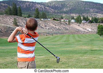 Young golfer playing a shot from the tee box