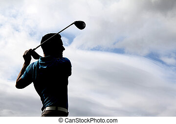 Young golfer driving with a wood against cloudy skies