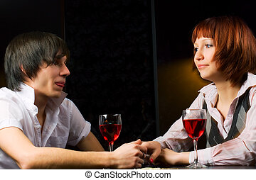 Young couple in a bar - Young couple drinking red wine in a...