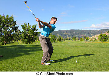 Tee shot - Young male golfer hitting a driver from the...