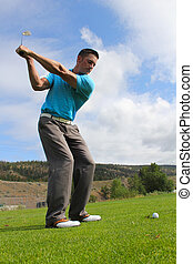 Fairway Shot - Young golfer hitting a fairway shot with an...