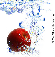 red apple under water with a trail of transparent bubbles.