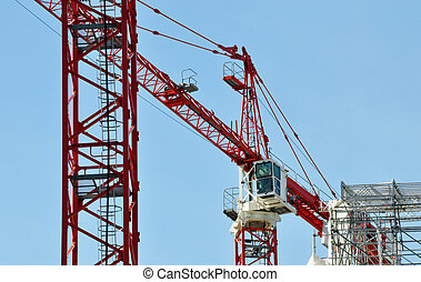 Cranes on a construction site, blue sky in the background