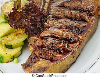 t bone steak - grilled t-bone steak and vegetables , close...