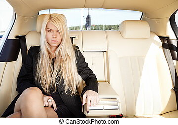 Lady in a luxury car - Young blond lady sitting on a...