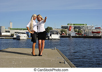 Two girls blonde stand on the pier and point a finger