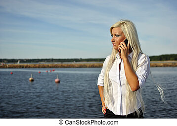 girl talking on a cell phone on the beach - blonde girl...