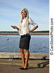 Girl with mobile phone on the beach - Blonde girl standing...