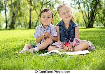 Children in the park reading a book - Sister and brother in...