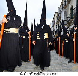 Processions of Nazarenos walk the streets at night during...