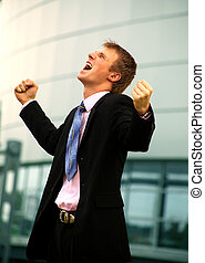 business man standing with fists clenched in victory.