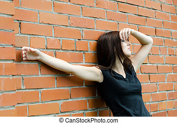 Young sad girl at brick walls - The young sad girl at brick...