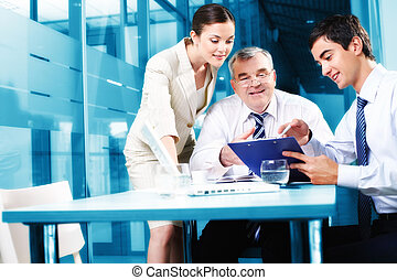 Business plan - Young manager showing plan to his colleagues...