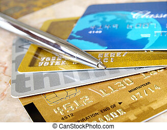 Credit cards. - Silver pen on the pile of credit cards .
