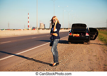 Woman calling for help - Young blonde with a broken car on...