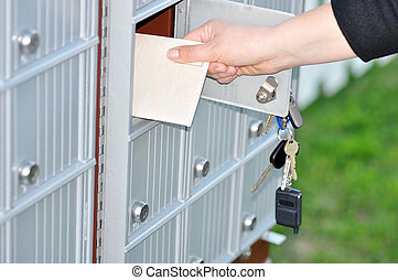 Getting the mail - Hand retrieving a letter from the...