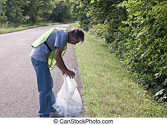 roadside cleanup - man picking up trash along a rural road