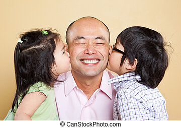 Asian father and kids - A shot of an Asian father kissed by...