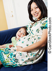 Pregnant Asian mother and her daughter - A shot of a...