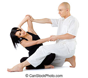 Thai massage stretching - Young female sitting and receiving...