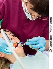 Dentist working patient - Female dentist with gloves and...