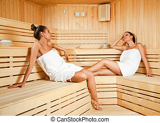 Females relaxing in sauna - Beautiful young females relaxing...