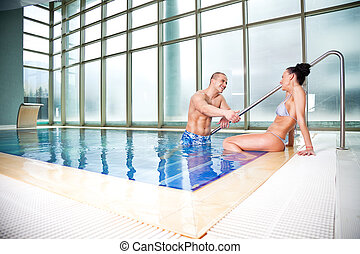 flirting couple swimming pool - Young attractive couple...