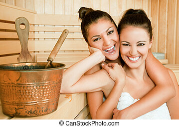 females hugging sauna - Two beautiful happy females with...