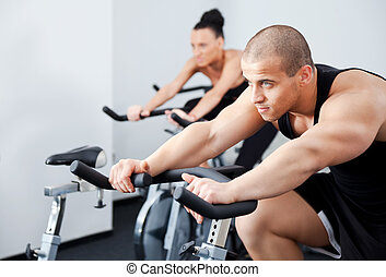 man spinning veloargometer gym - Young athletic couple...